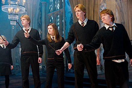 Ron Weasley and his siblings stand with wands posed in Harry Potter and the Order of the Phoenix.